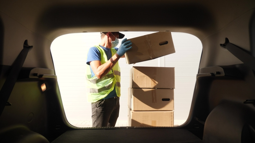 driver worker coronavirus. loader wearing a medical mask delivers goods during the coronavirus period. driver worker coronavirus. courier driver in gloves loads boxes during coronavirus Royalty-Free Stock Footage #1057955194