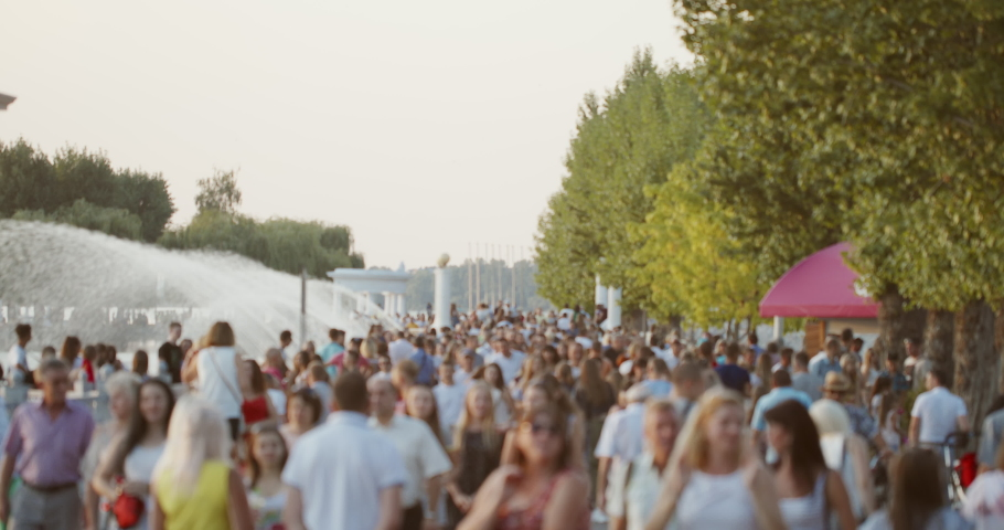 Crowd of people walking on park alley near fountain and green trees in summer evening in city - face people blur Royalty-Free Stock Footage #1057961974