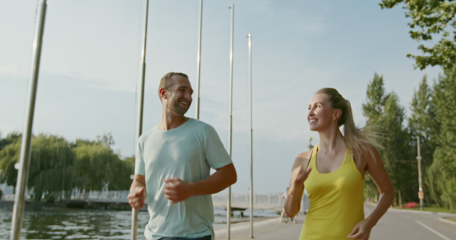 Happy couple running near water, tracking shot of delighted sportsman and sportswoman running on embankment near water during fitness training on summer day, slow motion | Shutterstock HD Video #1057961977