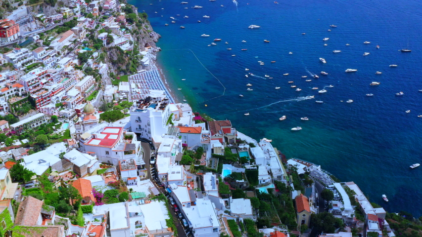 Aerial Drone View of Positano, near Naples, Italy. Historic White town along the Amalfi Coast Near Salerno. High view of the Beach and Blue Ocean with boats.
