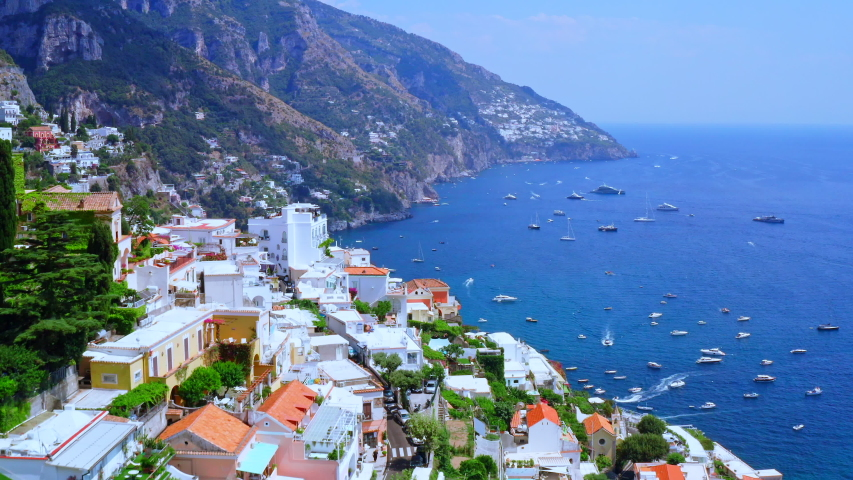 Aerial Drone View of Positano, near Naples, Italy. Flying Low above Historic White town along the Amalfi Coast Near Salerno. View of the Beach and Beautiful Blue Ocean with boats.