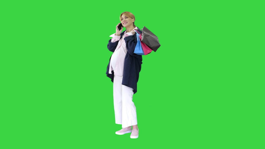 Happy pregnant woman shopping and speaking by phone holding bags on a Green Screen, Chroma Key.