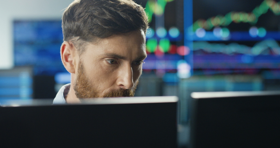 Close up of young Caucasian mman trader working at monitor computer and browsing online in trading office. Male broker following rates and bets. Manager texting at screen.