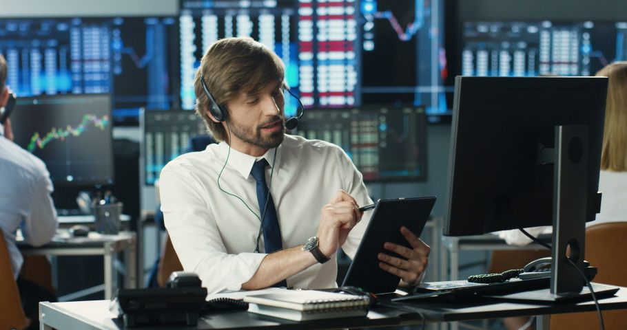 Caucasian man broker in headset sitting in front of computer monitor talking with client. Tapping on tablet device. Male trader speaking, buying, selling stocks. Call center. Customer support Royalty-Free Stock Footage #1057979551