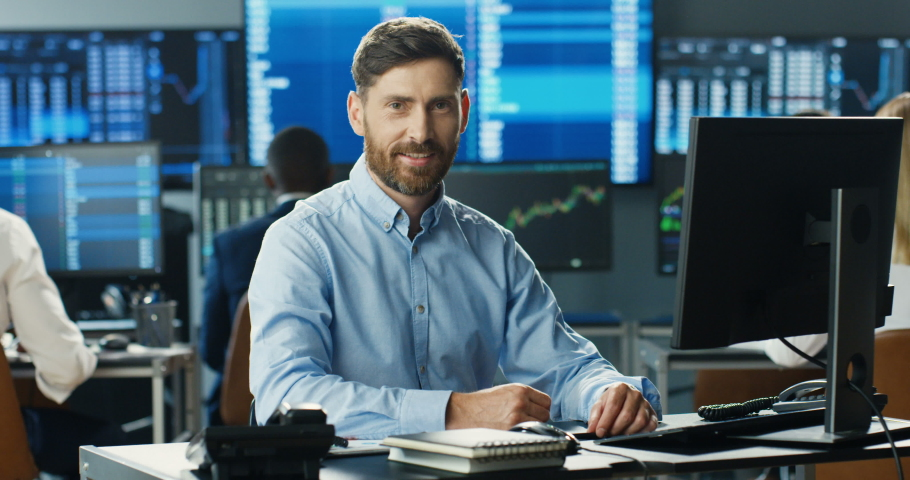 Portrait of young Caucasian handsome man trader working at computer, looking at camera and smiling in trading office of stock market. Happy cheerful male successful broker with smile. Businessman. Royalty-Free Stock Footage #1057979554
