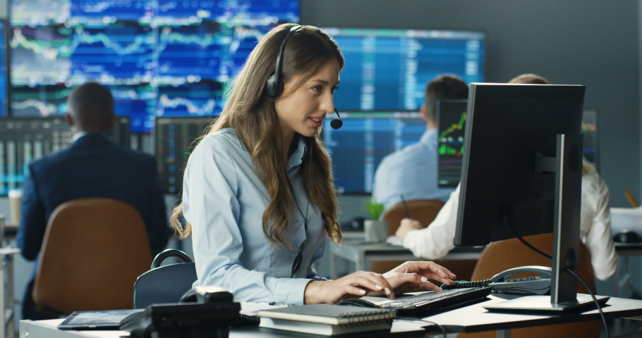 Young Caucasian pretty woman trader in headset working at monitor of computer in trading office and talking with client. Female broker typing on keyboard and speaking with customer. Sales call center. Royalty-Free Stock Footage #1057979563