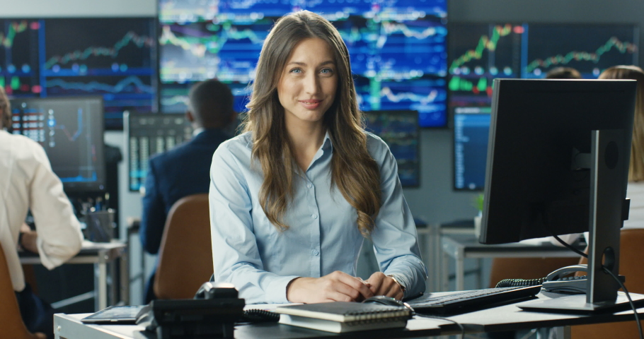 Portrait of young Caucasian beautiful woman trader working at computer, then looking at camera and smiling in trading office of exchange stock market. Female successful broker with smile on face. Royalty-Free Stock Footage #1057979569