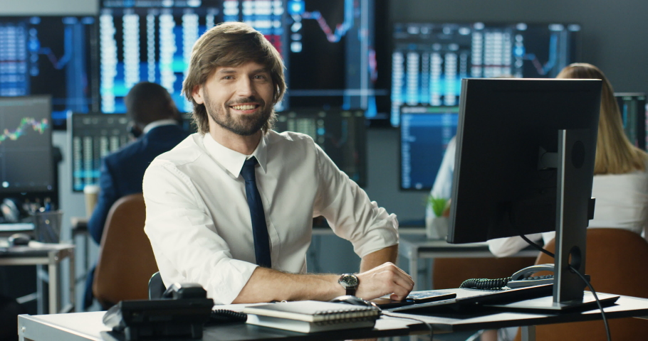 Portrait of young Caucasian handsome man trader working at computer, then looking at camera and smiling in trading office of exchange stock market. Happy cheerful male successful broker with smile. Royalty-Free Stock Footage #1057979575
