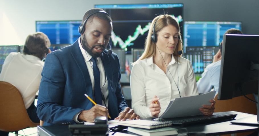Mixed-races couple. Male and female traders working together in headsets at desk, writing notes on papers. Talking with clients. Trading market office. Multiethnic man and woman noting in call center. Royalty-Free Stock Footage #1057979674