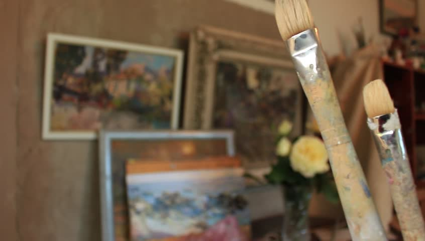 Paintbrushes on Art workroom background. Oil painting material close up. Pan.