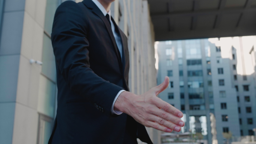 Close-up handshake of business people. Concept of greeting or closing a deal. Two businessmen shaking hands outdoors on the background of a modern business office building.