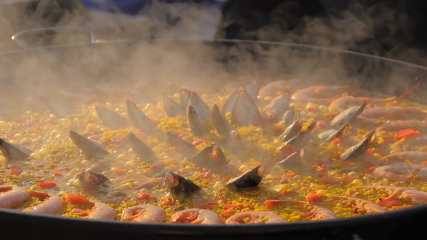 Slow motion: process of cooking paella with shrimp, mussel, rice, spice, saffron in huge paella pan at summer outdoor food market: close up. Spanish cuisine, seafood, gastronomy, street food concept Royalty-Free Stock Footage #1057992151