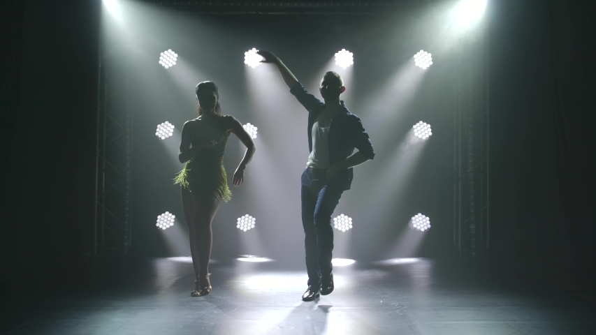 Young couple dancing latin music. Bachata, merengue, salsa. Shot in a dark studio with neon lights in the background.