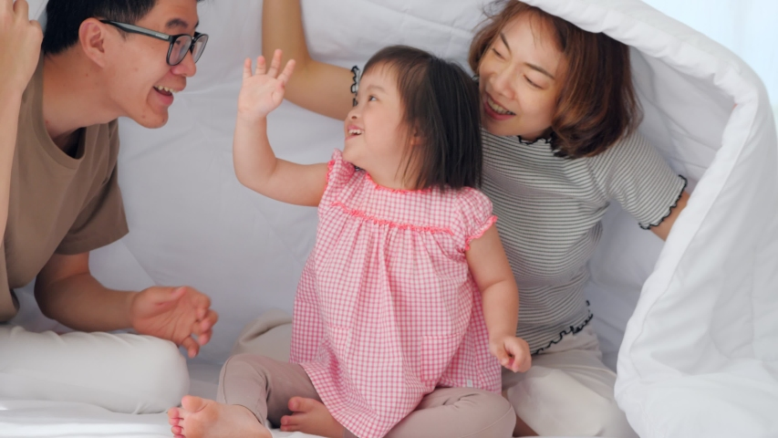 Happy family with mother, father and disabled daughter spending time together in bedroom. Royalty-Free Stock Footage #1057997398