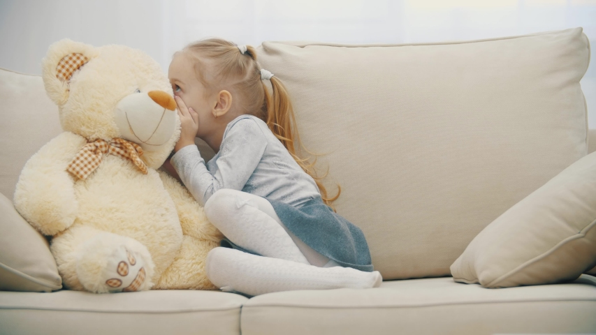 4k slowmotion video of little girl sitting on the sofa, talking with her teddy and showing silent sign. | Shutterstock HD Video #1057997431