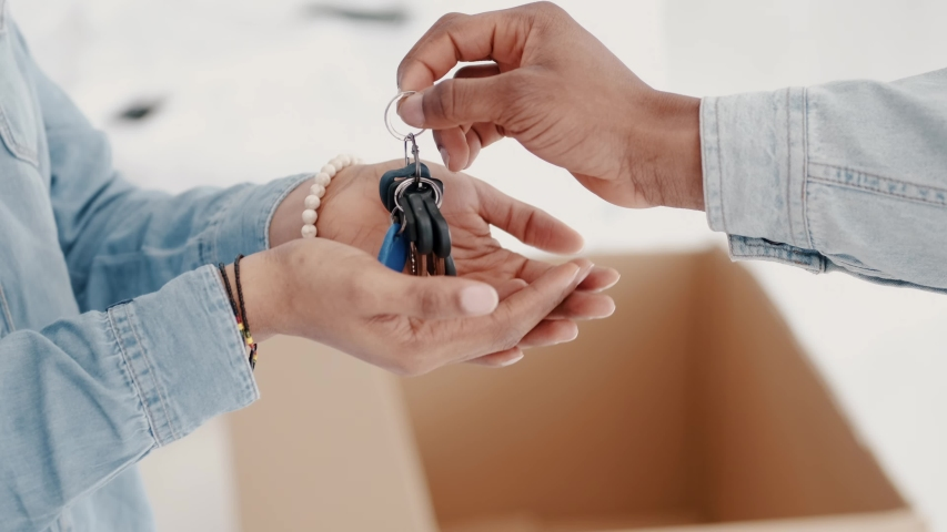 Two people are holding home keys. The African marriage have moved in a new house. | Shutterstock HD Video #1057997785