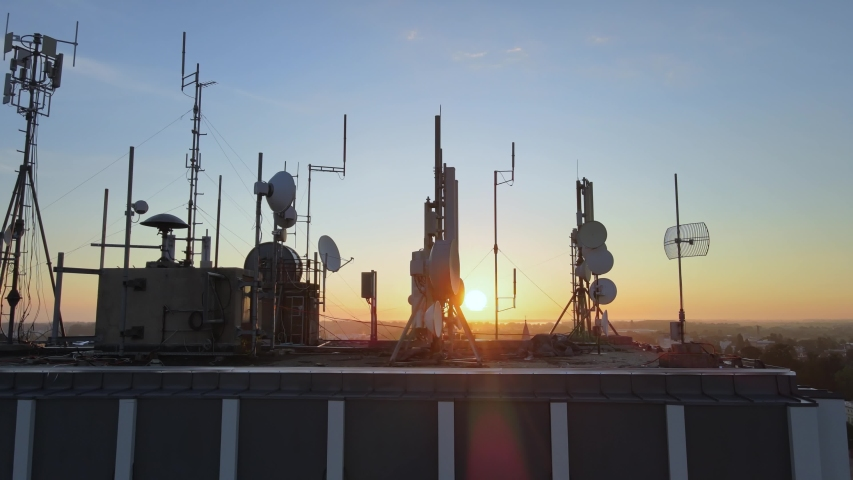 Silhouette of electromagnetic towers with satellite dish, microwaves and panel antennae at rooftop station during golden. Motion footage. Royalty-Free Stock Footage #1058005933