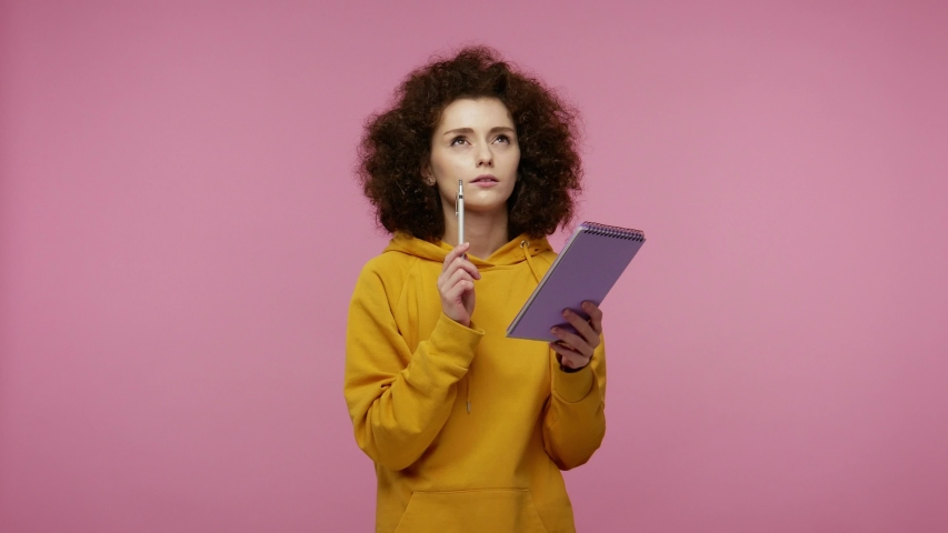 Thoughtful creative young woman afro hairstyle in hoodie thinking over future business plan, taking notes in paper notebook, writing creative idea and smiling inspired happy. indoor isolated