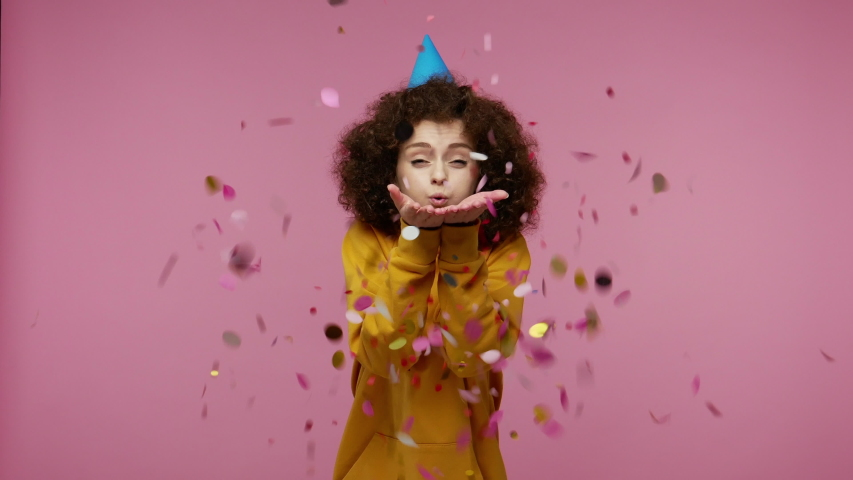 Young woman afro hairstyle in hoodie with funny cone on her head laughing, moving in dance and blowing confetti glitters, celebrating birthday congratulating on anniversary. studio shot isolated | Shutterstock HD Video #1058012833