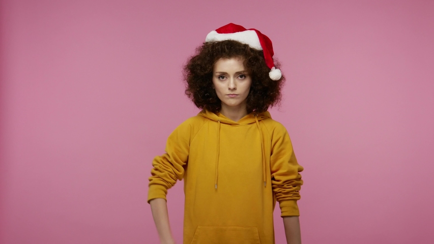 Funny positive young woman afro hairstyle with Santa Claus hat dancing and singing, feeling carefree happy, moving in energetic dance, relaxing on Christmas party. indoor isolated on pink background | Shutterstock HD Video #1058012836