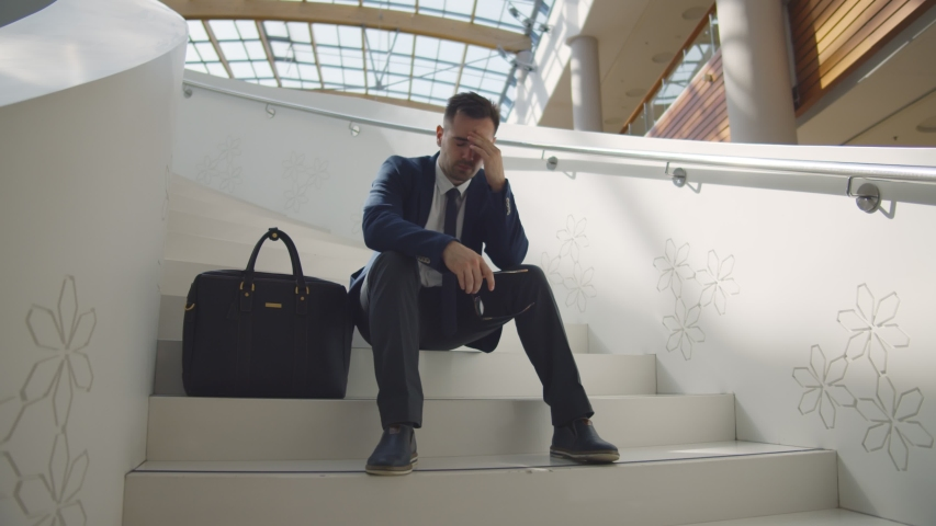 Dismissed businessman frustrated and desperate sitting on staircase in business center. Unhappy young entrepreneur sitting on stairs worry about financial crisis and unemployment