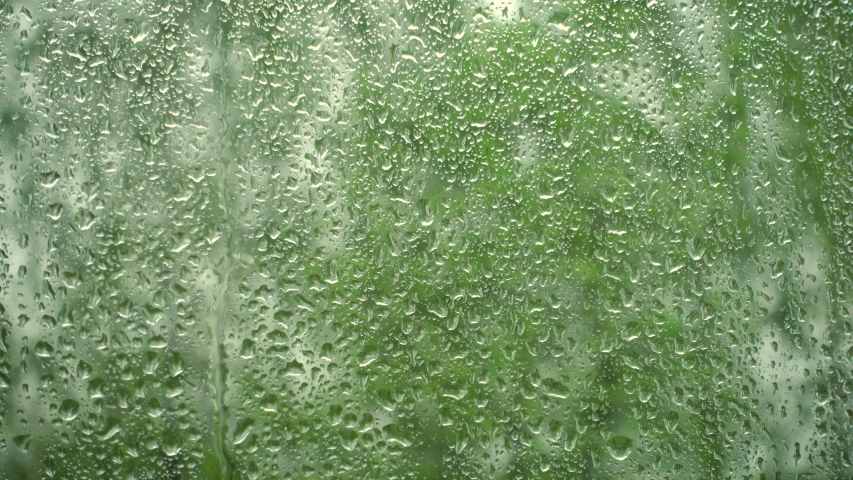 Rain on the window. Raindrops on a window and green trees outside the window. | Shutterstock HD Video #1058018833