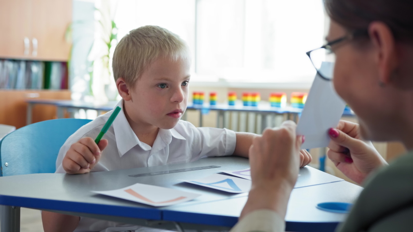 life with disabilities, boy with downs syndrome studying mathematics with her teacher sitting at desk in classroom at elementary school Royalty-Free Stock Footage #1058021317