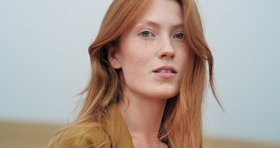 Portrait of Mysterious Ginger Woman is enjoying Nature on Field. Amazing Red-Haired Woman is touching her long Hair, having Amazing Blue Eyes. Looking Happy, feeling Liberty at Countryside. Royalty-Free Stock Footage #1058021614