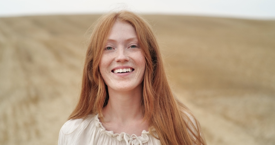Cute Ginger Woman with long Red Hair walking on the Field, looking at Camera. Happy Ginger Girl is spinning ti the Camera with happy Smile, Summer Face Female. Emotions. People. Portrait. Royalty-Free Stock Footage #1058021620