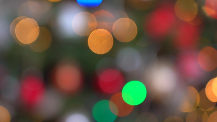 Shimmering abstract colored circles defocused christmas lights video. Blurred fairy lights. Out of focus holiday background christmas tree. Light bokeh from Xmas tree. Xmas and New Year theme. 4k  | Shutterstock HD Video #1058024920