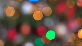 Shimmering abstract colored circles defocused christmas lights video. Blurred fairy lights. Out of focus holiday background christmas tree. Light bokeh from Xmas tree. Xmas and New Year theme. 4k