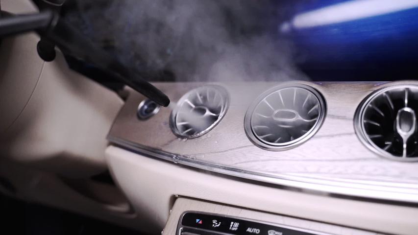 Zooming FHD shot of a hot steam cleaner cleaning the air conditioning vents in a futuristic car dashboard, with hot steam coming out of the vents. Hot steam cleaning of a car dashboard ventilation.