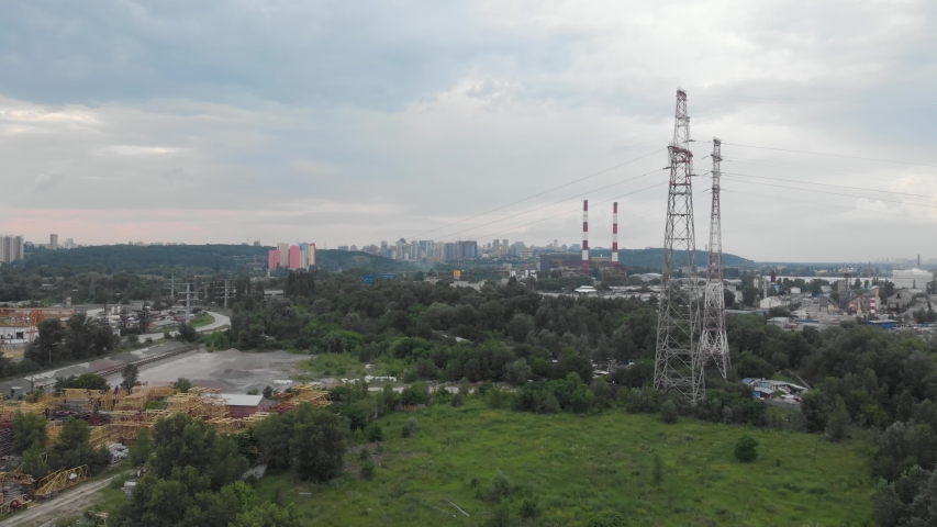 High voltage power line pylons in industrial city area. Transmission power in Kyiv Ukraine suburb outskirt aerial shot. | Shutterstock HD Video #1058029669