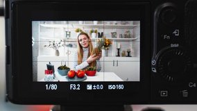 Camera screen recording - Food blogger cooking fresh vegan salad of fruits in kitchen studio, filming tutorial for video channel. Female influencer holds apple, pineapple, talks about healthy eating.
