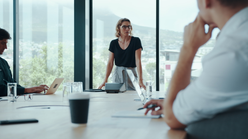 Female entrepreneur explaining new strategies to colleagues in meeting room. Businesswoman discussing work with team in boardroom.  Royalty-Free Stock Footage #1058030683