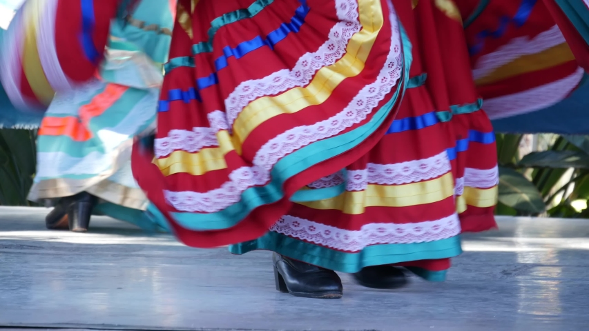 Latino women in colourful traditional dresses dancing Jarabe tapatio, mexican national folk hat dance. Street performance of female hispanic ballet in multi colored ethnic skirts. Girls in costumes.