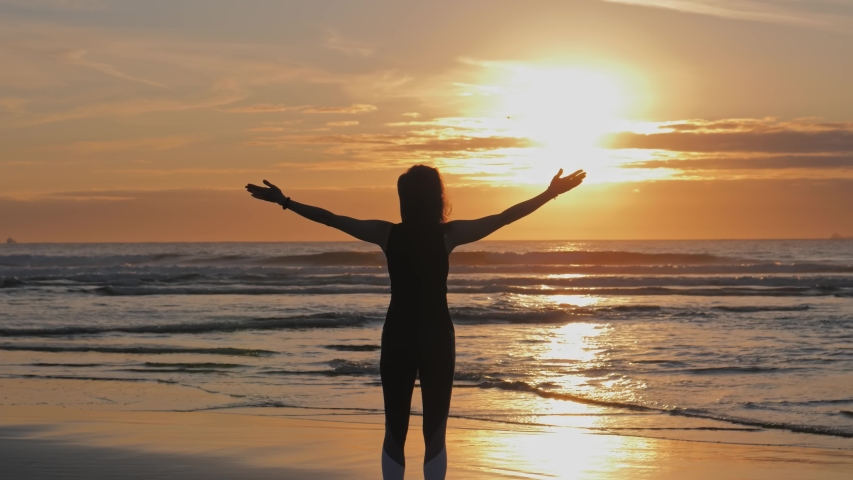 Silhouette of slim woman with arms raised up on the beach at beautiful sunset, Practice of breath techniques   Shutterstock HD Video #1058037766
