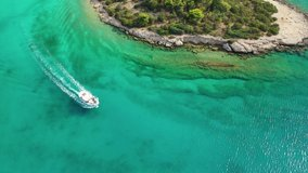 Aerial bird's eye view video taken by drone of boat cruising in Caribbean tropical rocky beach with turquoise - sapphire waters