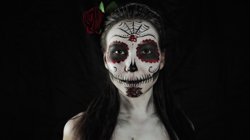 Mexican day of the dead. Young woman with sugar skull Halloween makeup looking at the camera and smiling. Extreme close-up. Happy Halloween. Royalty-Free Stock Footage #1058048917