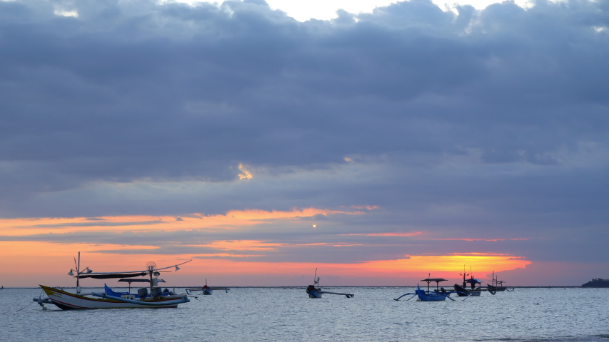 Beautiful colorful sunset with traditional balinese fishing boats in lagoon with landing airplaine in background sky
