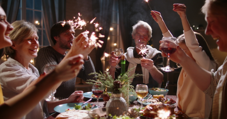 Large happy caucasian family celebrating christmas or new year together, holding sparklers at party dinner table and making wishes - celebration concept 4k footage