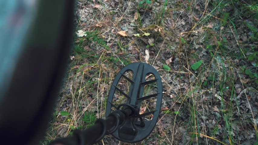 Man walks with a metal detector in the woods. the view from the top