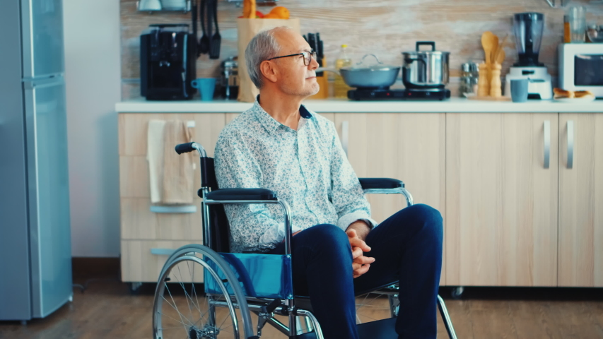 Paralysed senior man in wheelchair feeling unhappy. Elderly handicapped pensioner after injury and rehab, paralysis and disability for depressed invalid full of sorrow, worry and sad face. Retirement   Shutterstock HD Video #1058055544