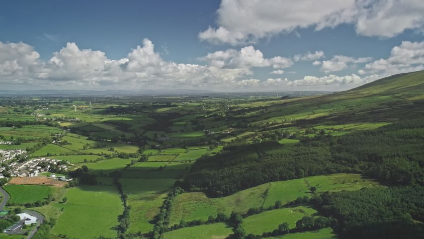 Hyperlapse Ireland rural scape aerial view: farmlands fields and cityscape with white houses, roads, ways. Irish nature variety in coast Ballycastle port town, Antrim County. Footage shot in FullHD