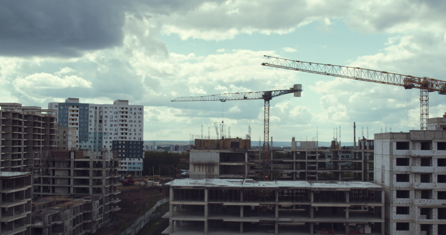 Building site with high-rise block under construction in an urban environment dominated by a large industrial crane silhouetted against a cloudy blue sky. | Shutterstock HD Video #1058061238