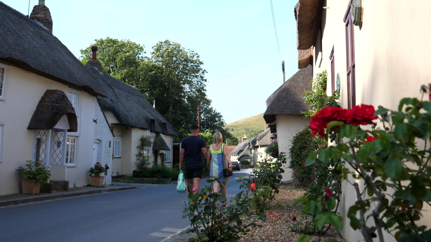 A young couple walking hand in hand in an old English village | Shutterstock HD Video #1058069113