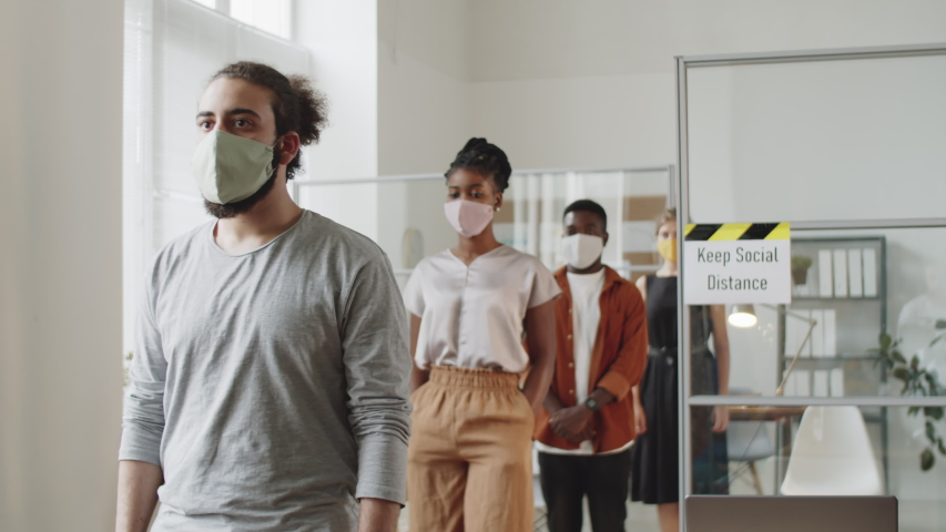 Multiethnic male and female employees in protective masks walking one by one through open space office and keeping social distance while working during covid-19 pandemic Royalty-Free Stock Footage #1058069797