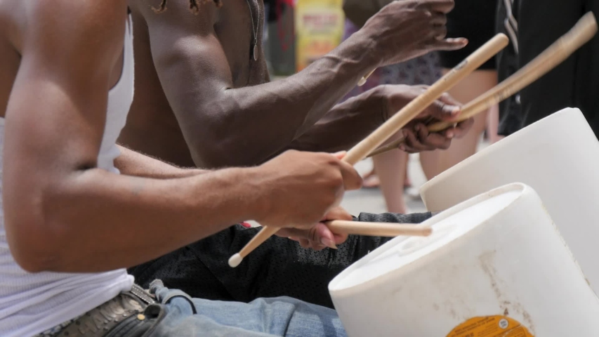 Close up of street performers/buskers drumming on plastic containers.