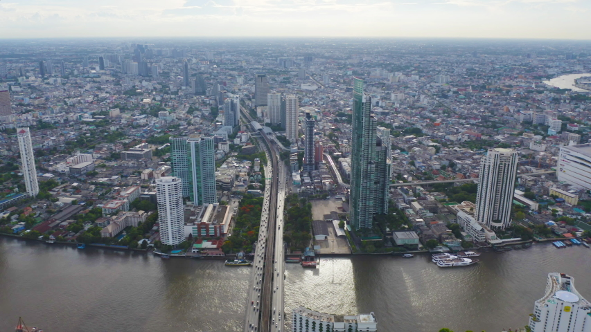 Aerial view of Bangkok Downtown Skyline with Chao Phraya River. Thailand. Financial district and business centers in smart urban city in Asia. Skyscraper and high-rise buildings at sunset. | Shutterstock HD Video #1058072137