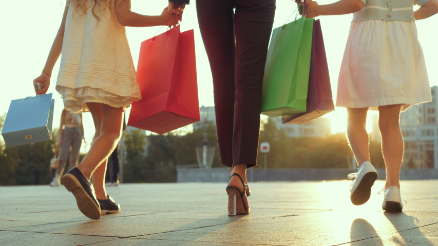 Close up of woman legs walking down street with two little girls. Mom with daughters returns from shopping, holds children by hands, carries bags of gifts shopping, modern family spends time together Royalty-Free Stock Footage #1058072929